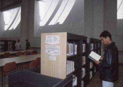 Usuario en las estanterías de la Biblioteca Pública El Tintal Manuel Zapata Olivella