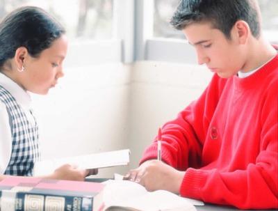 Jóvenes usuarios escolares estudiando en una biblioteca